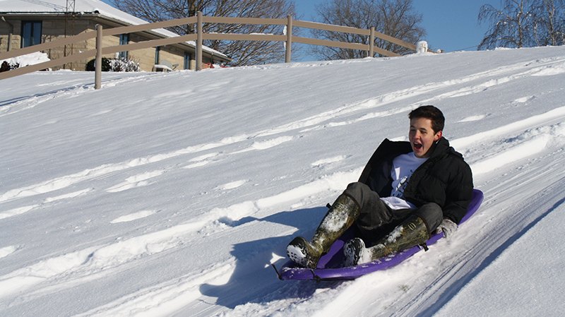 Brazilian exchange student sledding for the first time
