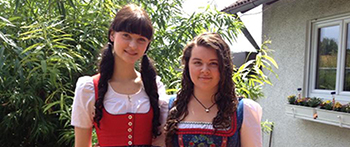 German exchange student with her American host sister, wearing traditional German clothing.