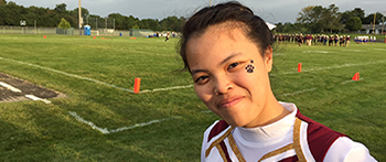 PAX exchange student from Thailand wearing her cheerleading uniform during a football game at her Minnesota high school