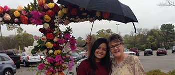PAX exchange student from Brazil sharing an umbrella with her host mom on a rainy Easter Sunday in Alabama