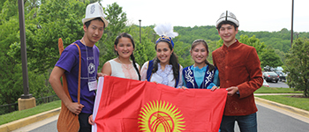International high school students from Kyrgyzstan in traditional dress holding Kyrgyz flag at conference for cultural understanding
