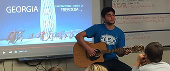 Exchange student from Georgia playing his guitar and singing during International Education Week
