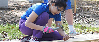 YES international student from Pakistan hammers a nail into a decking board while volunteering with Habitat for Humanity