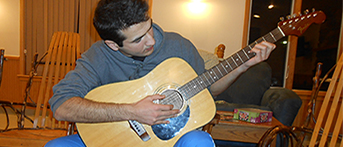 PAX exchange student from Tajikistan playing the guitar at a leadership event