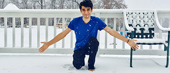 YES exchange student from Pakistan kneeling in his first snow on the deck of his Wisconsin home