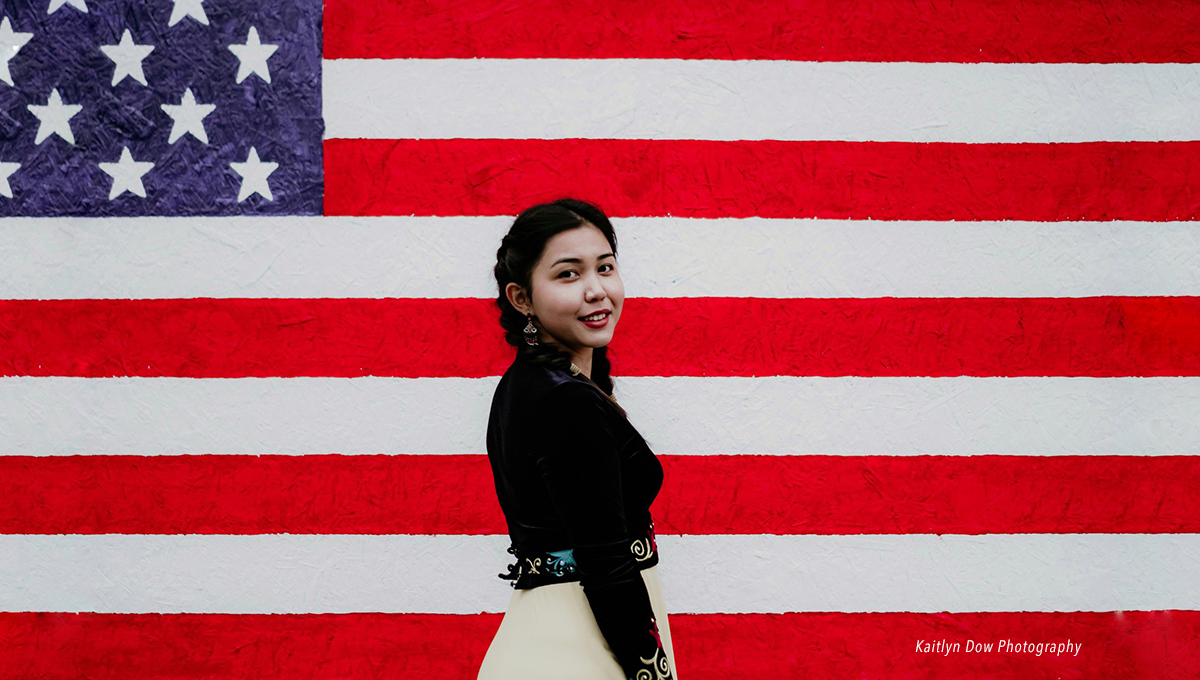 International high school student standing in front of mural depicting the American flag