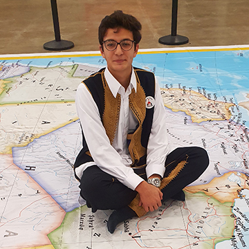 Libyan high school exchange student in traditional dress, sitting on map of world