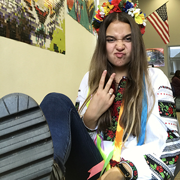 Teenage girl with traditional Ukrainian dress giving the peace sign