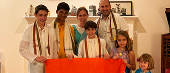 Exchange student from India with American host family in traditional clothing and Indian flag