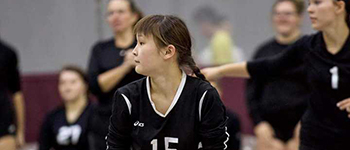 Future Leaders Exchange Program student from Kyrgyzstan ready for a bump in a high school volleyball game