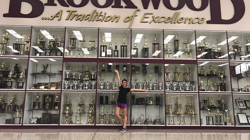 PAX exchange student from Germany poses in front of her high school's trophy display case in Georgia