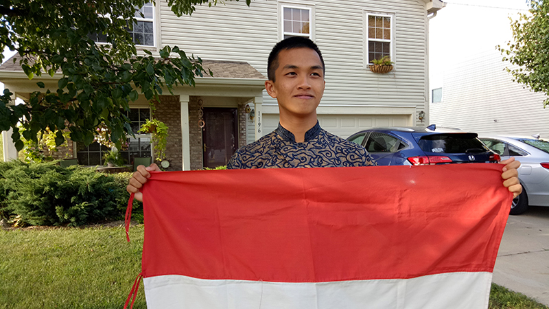 International student waves Indonesian flag in front of his host family's home in Indiana