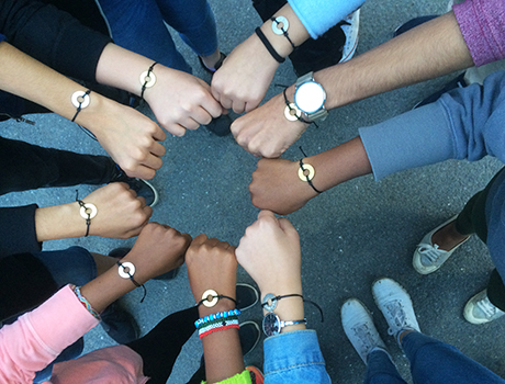 Multi-cultural group of FLEX, YES, and Abaarso scholarship students display their bracelets