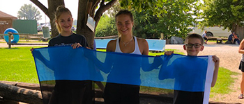 FLEX high school exchange student holding Estonian flag with her host siblings in Illinois