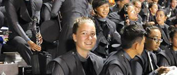 Foreign exchange student from Germany sits in the bleachers with the band holding her flute during a football game