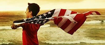 Foreign exchange student from Azerbaijan holding the American flag during a family trip to the Pacific coast