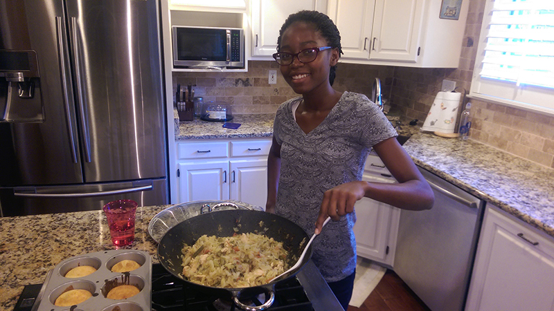 High school exchange student in the USA cooks a Cameroonian meal in the kitchen of her Tennessee host family