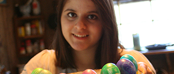 Kennedy Lugar Youth Exchange and Study program participant from Pakistan shows her decorated Easter eggs to the camera