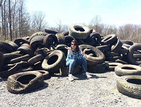 Exchange student from Pakistan sits on a pile of tires she pulled from a ravine in Pennsylvania with her host father