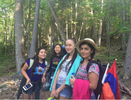 Foreign exchange students from Lebanon, Kazakhstan, and Mexico hiking through the woods of Maine during a field trip