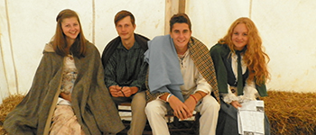 PAX exchange students from Serbia, Ukraine, Russia, and Holland sitting in a tent during a historical re-enactment in Indiana