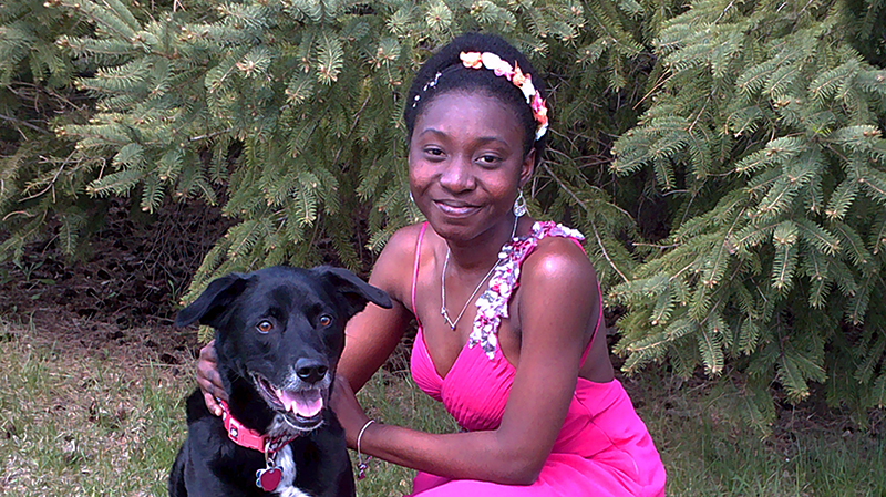 International high school exchange student from Ghana in formal dress with her host family's dog in Wisconsin