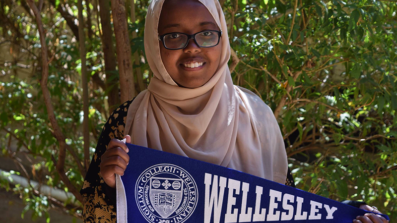 Abaarso School alumna and former exchange student from Somaliland holds Wellesley College pennant