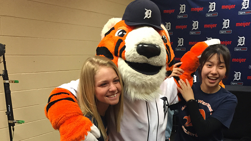 Chinese exchange student and her American friend with the Detroit Tigers' mascot after a baseball game